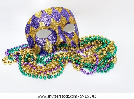 Horizontal image of green, gold and purple mardis gras beads and a purple and gold harlequin mask covered with glitter to commemorate the February celebration that is a huge holiday in New Orleans. - stock photo