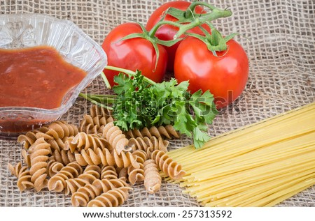 horizontal image of raw spaghetti and whole wheat pasta with tomato on the vine and a dish of salsa on burlap background.  - stock photo