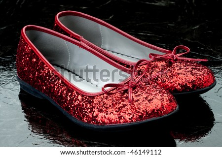 Horizontal image of sequined red slippers on dark tile. - stock photo