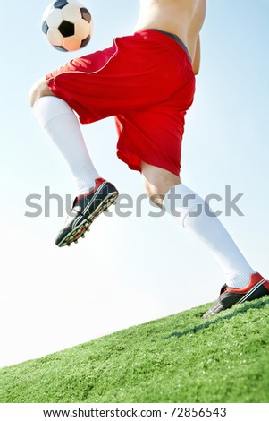 Horizontal image of soccer ball being kicked by footballer against blue sky - stock photo