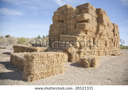 Horizontal image of stacks of bails of hay. - stock photo