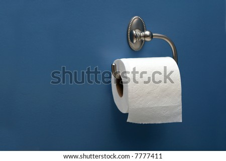 horizontal image of toilet paper on blue wall, right. - stock photo