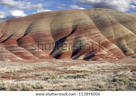 Horizontal landscape of the colorful Painted Hills in Oregon against cloudy blue skies. - stock photo