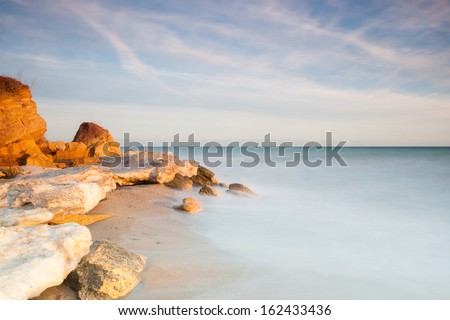 Horizontal long exposure shot of a shore with rocks covered in snow during a sunset - stock photo