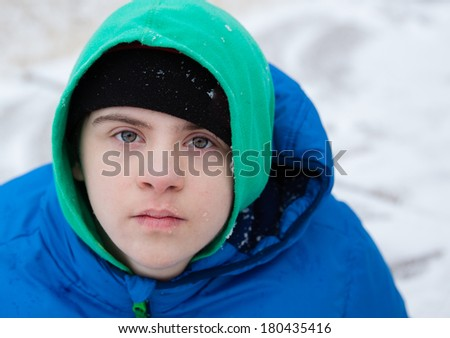 horizontal orientation close up of a boy with autism and down's syndrome dressed in a colorful hat, sweatshirt and jacket, with snowy background / Helping the child with Autism Dress Appropriately - stock photo