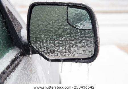 horizontal orientation close up of a car exterior mirror covered in thick ice, with copy space / Hazards of Winter Driving - stock photo
