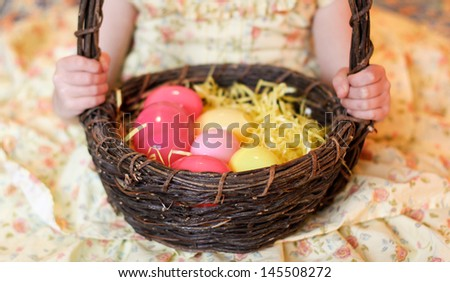 horizontal orientation close up of a little girl's hands holding a wooden  basket with brightly colored eggs and yellow grass / Basket of Surprises - stock photo