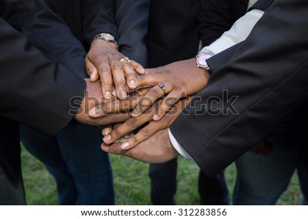 horizontal orientation close up of adult hands, wearing suits and business attire, stacked on one another in a show of unity and teamwork / Building Teamwork and Trust - stock photo