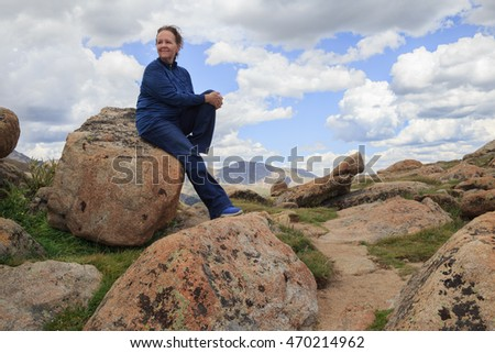 horizontal orientation color image of a single, happy, older woman hiker stopping to rest on a large boulder against a cloudy blue sky / High Altitude Hiking Senior Woman