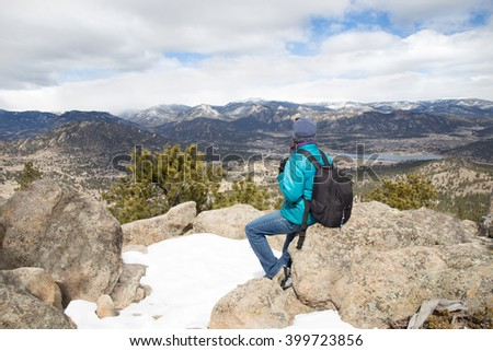 horizontal orientation color image of a single woman hiker in winter, gazing out at the Rocky Mountain Range as she rests on a rock / Spectacular View at Trail's End in Winter - stock photo
