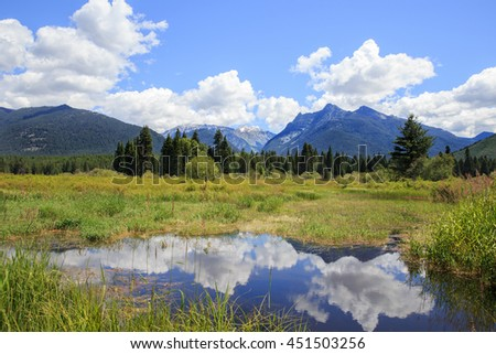 horizontal orientation color image of the Cabinet Mountains in Montana, USA with a small pond in the foreground relecting the cloudy sky / The Cabinet Mountains