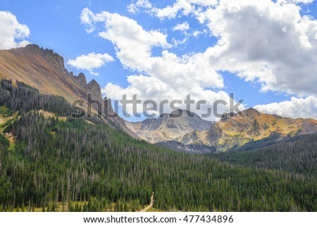 horizontal orientation color image of the Rocky Mountains at high elevation, with blue skies and clouds / The Rocky Mountains on a Cloudy Day