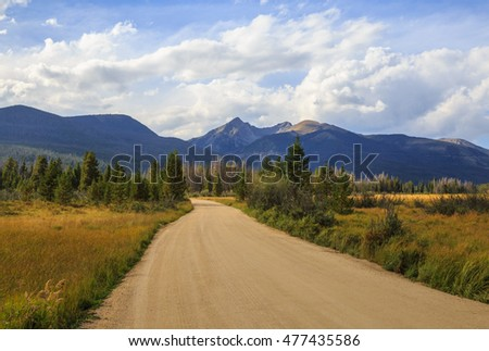 horizontal orientation color image with a dirt road in the foreground, and the Colorado Rocky Mountains in the background on a cloudy day / Road to the Rockies