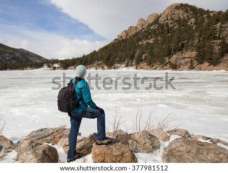 horizontal orientation image with a single woman hiker with backpack, in winter clothing and crampons, looking over a frozen lake / Lake Lily in Winter with Woman Hiker - stock photo