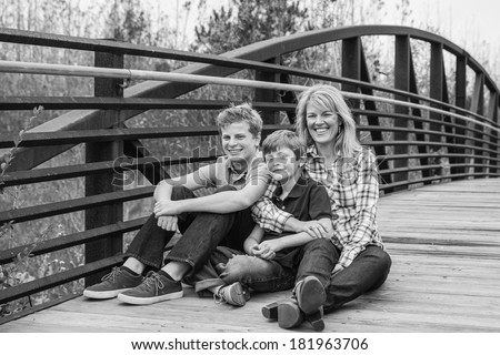 horizontal orientation of a beautiful woman sitting with her two sons outside on a bridge in black and white with copy space / Making Time for Each Other - stock photo