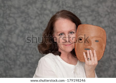 horizontal orientation of a single woman with a slight smile holding a clay mask in one hand with neutral  grey background and copy space / Masking the Symptoms of Mental Illness - stock photo