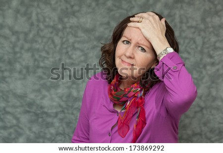 horizontal orientation of a woman in brightly colored business attire holding her head in her hand with copy space and neutral background / My Head Hurts - stock photo