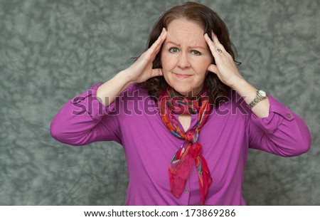 horizontal orientation of a woman in brightly colored business attire with a look of pain while she holds her head with both hands / Business Woman with a Headache - stock photo