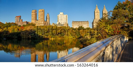 Horizontal Panoramic of Central Park in fall. View from the Bow Bridge over the Lake, Central Park trees and Upper West Side buildings in autumn. Urban photography, Manhattan, New York City. - stock photo