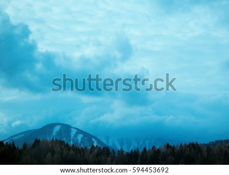 Horizontal photo depicting a beautiful moody frosty landscape European alpine mountains with snow peaks on a blue cloudy sky background.