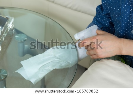 Horizontal photo female hands wiping underneath glass round end table with spraying cleaning solution bottle and paper towels in hand with sofa and partial lamp in background  - stock photo