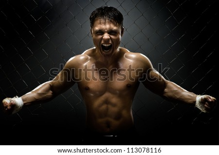 horizontal photo  muscular young  guy street-fighter,  aggression frightening  yell , hard light - stock photo