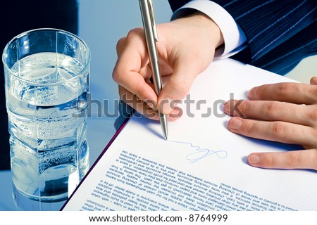 Horizontal photo of a businessman's hands signing a contract with a glass of water on the backgrounds - stock photo