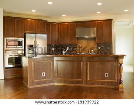 Horizontal photo of a modern residential kitchen with stone counter tops, stainless steel appliances, cherry wood cabinets and hardwood floors