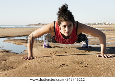 Horizontal photo of a young woman doing pushups on the beach. - stock photo