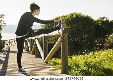 Horizontal photo of a young woman stretching on the railing of the path leading to the beach.