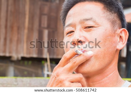 horizontal photo of asian addict man smoking cigarette.