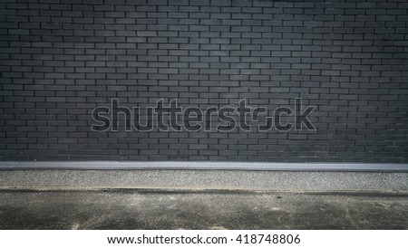 Horizontal photo of concrete floor and black brick wall. Place for text