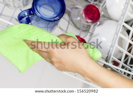 Horizontal photo of female hand cleaning upper dish rack with green microfiber rag from dishwasher with blue, red, clear glasses and white bowls in background - stock photo