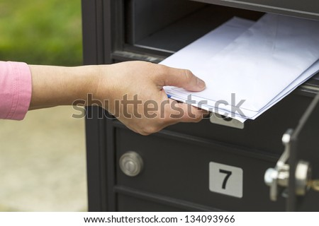 Horizontal photo of female hand pulling out letters from postal mailbox with green grass and sidewalk in background - stock photo