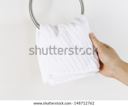 Horizontal photo of female hand putting clean white towel on wall hook  - stock photo