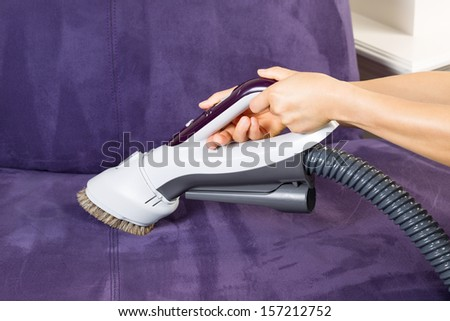Horizontal photo of female hands holding vacuum cleaner extension for cleaning suede leather couch  - stock photo