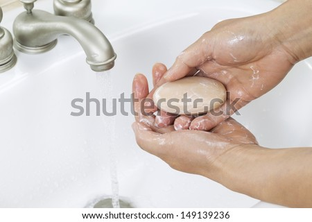 Horizontal photo of female hands lathering up with bar of soap, running water and bathroom sink in background - stock photo