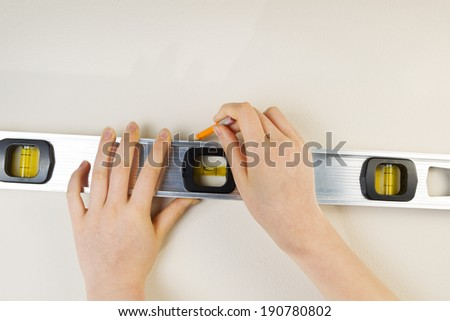 Horizontal photo of female hands using level and pencil on interior white wall - stock photo