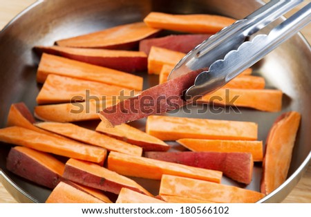 Horizontal photo of freshly cut Yams in stainless steel frying pan with focus on single piece being place into pan with tong - stock photo