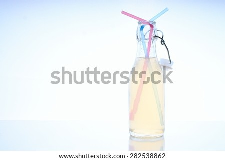 Horizontal photo of glass bottle with cold drink on glass board table with two color straws inside. Reflection of bottle is visible below. - stock photo