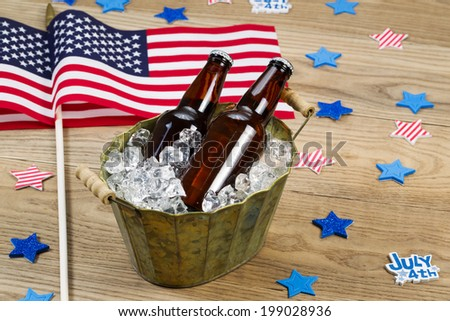 Horizontal photo of glass bottled beer in old metal bucket filled with ice and American flags in background for celebration of Independence Day - stock photo