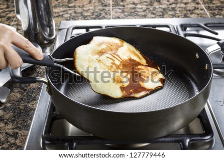 Horizontal photo of main focus on pancake being flipped in hot frying pan on top of gas stove range - stock photo