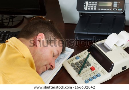 Horizontal photo of mature man relaxing, head position on tax forms, while working on his taxes with calculator with other office equipment in background