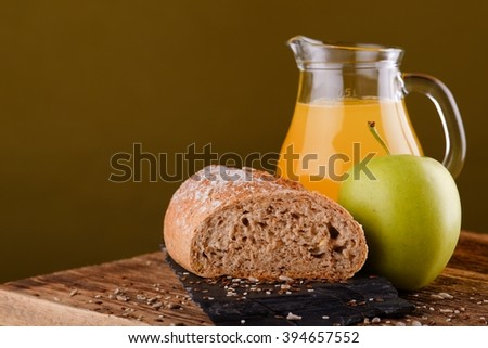 Horizontal photo of old wooden board with orange juice in glass jar, green apple and piece of cereal bread which is on black flat stone. Few sesame and flux seeds are spilled around. - stock photo