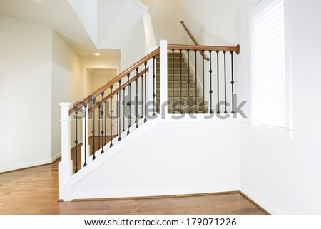 Horizontal photo of residential hard wooden floors and custom staircase made of iron and wood railing with carpet on steps - stock photo