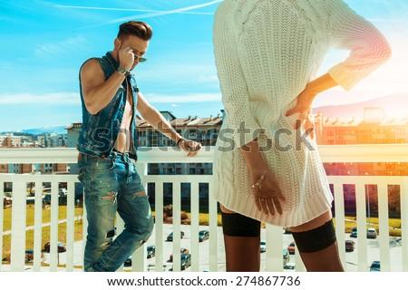 Horizontal photo of sexy fashionable man and seduce woman backside on balcony - stock photo