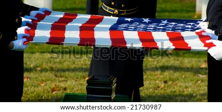 Horizontal photo of US flag held over funeral urn at burial ceremony at Arlington National Cemetery - stock photo