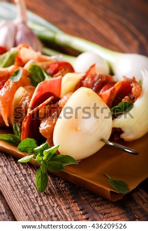 Horizontal photo of violet garlic bud in front of two skewers. Skewers on metal pin with onion, pork and chicken meat and sausage with peppers. Skewers on piece of brown paper on old wooden board. - stock photo