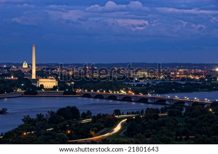 Horizontal photo of Washington DC at twilight with Capitol, Washington Monument and Lincoln Memorial in line with Potomac River in foreground