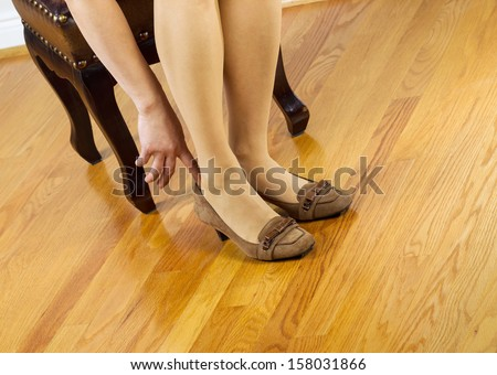 Horizontal photo of woman, wearing stockings, putting on dress shoes while sitting on leather padded footstool with red oak floors in background  - stock photo